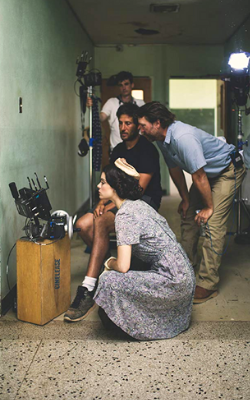 Leading lady Ali Cobrin (in foreground) and director Ty Roberts (hands on hips) watch playback of film footage on location during production of The Iron Orchard.
